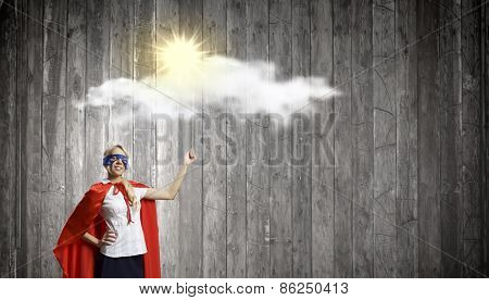 Young woman in super hero costume with bulb balloon in hand