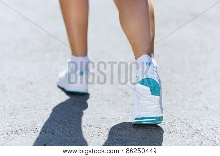Close up of female feet running on road