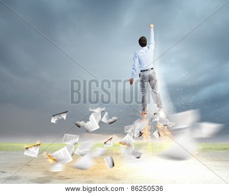 Rear view of businessman superhero flying up in sky