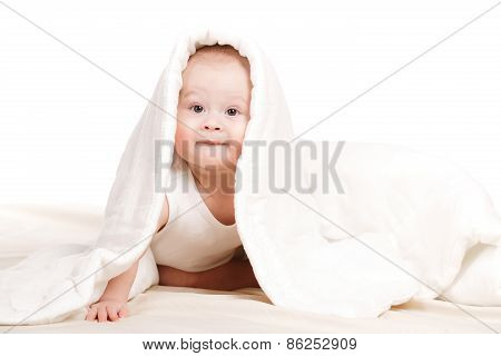 Cute baby peeking out from under the blanket,playing on the bed.