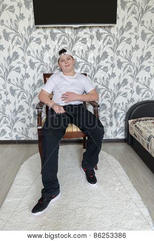 Teenager boy sitting on a chair in  living room