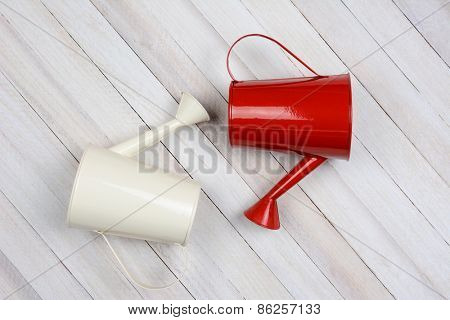 Two watering cans, one white another red laying on their side on a rustic whitewashed wood surface.