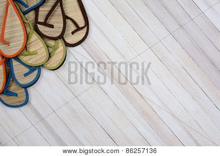 Summer sandals on a rustic white wood surface. The flip flops are set in the upper left side and corner of the frame leaving room for your copy.