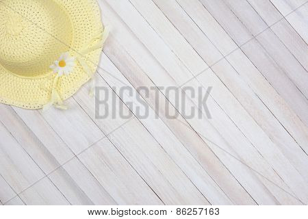 High angle shot of a yellow sun bonnet on a rustic wood surface. The hat is in the upper left corner of the frame leaving room for your copy.