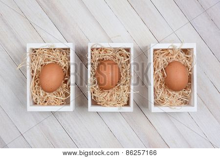 Three brown eggs in wood crates on a whitewashed wood surface. High angle shot in horizontal format.