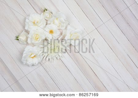 Overhead shot of a group of white flowers on a white wood table. Horizontal format with copy space.
