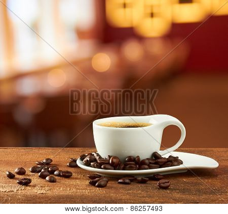 Warm Cup Of Coffee On Blur Cafe Background