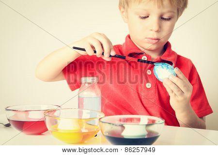 little boy painting eggs for easter