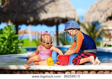 little boy and toddler girl playing at beach