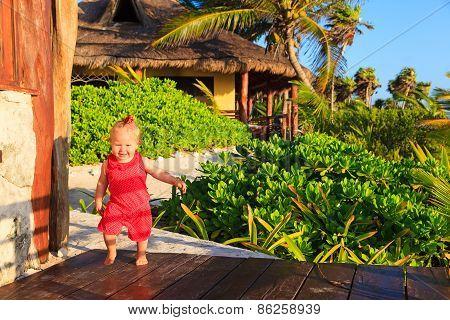 happy little girl walking in tropical resort
