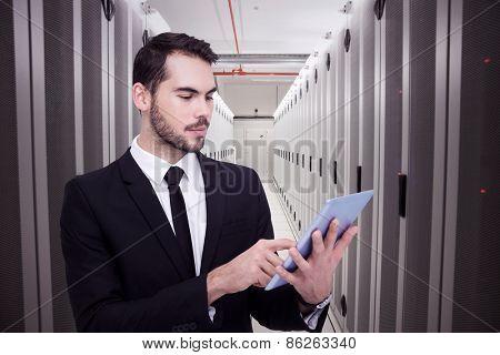 Cheerful businessman touching digital tablet against data center