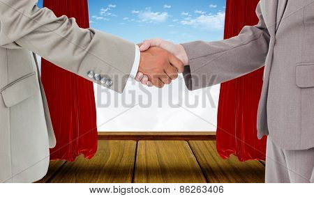 Side view of shaking hands against stage with red curtains