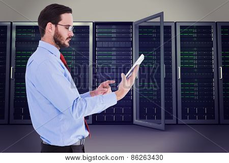 Businessman scrolling on his digital tablet against server towers