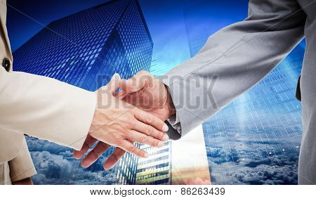 Close up of business people shaking their hands against low angle view of skyscrapers at sunset