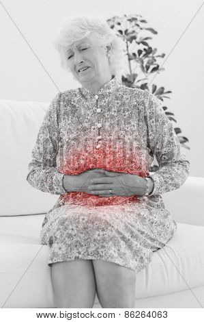 Elderly woman suffering with a belly pain in the living room