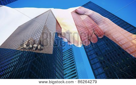 Close up of female and male hand shaking against skyscraper