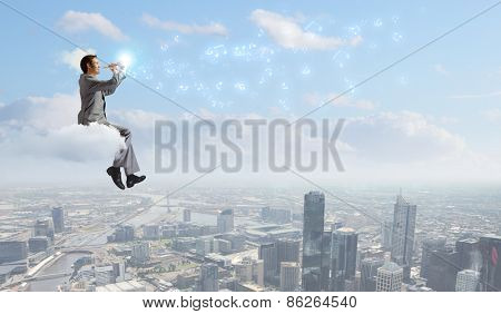 Young carefree businessman sitting on cloud and playing flute
