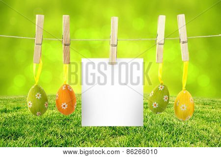 hanging easter eggs against field against glowing lights