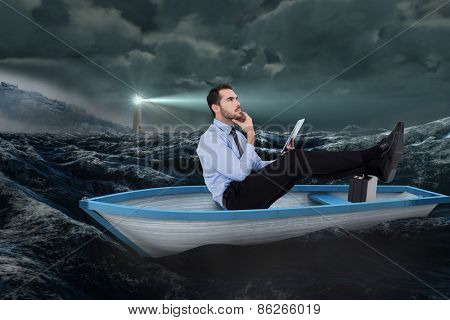 Businessman in boat with tablet pc against stormy sea with lighthouse