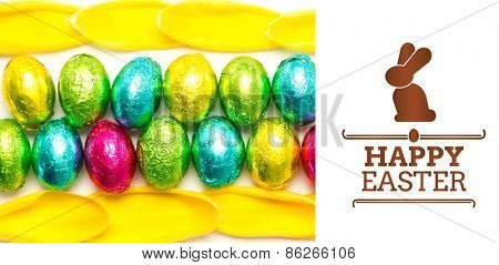 happy easter graphic against colourful foil wrapped easter eggs with tulip petals