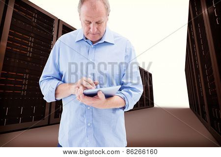 Mature man using his tablet pc against server hallway