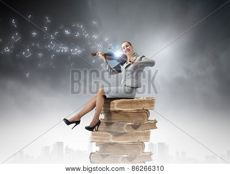 Young businesswoman sitting on pile of books and playing violin