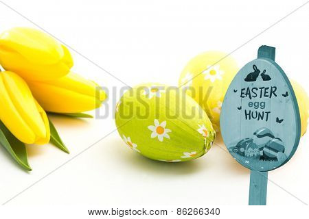 Easter egg hunt sign against three easter eggs with yellow tulips