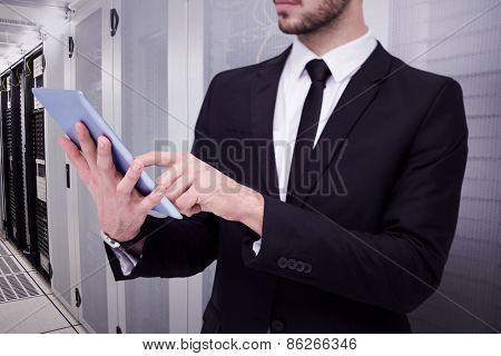 Mid section of a businessman using digital tablet pc against data center