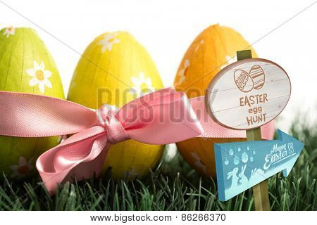 Easter egg hunt sign against three easter eggs wrapped in pink ribbon