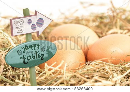 Easter egg hunt sign against three eggs nestled in straw