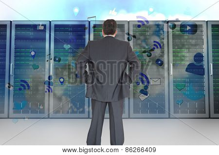 Businessman standing back to the camera with hands on hip against server towers