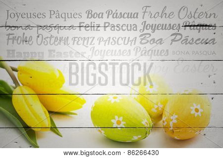 Happy easter in different languages against three easter eggs with yellow tulips