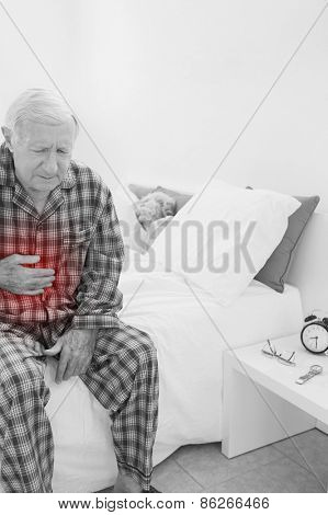 Old man suffering with belly pain in the bedroom