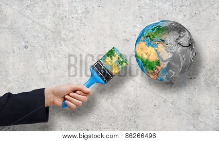 Close up of business person hand painting Earth planet. Elements of this image are furnished by NASA