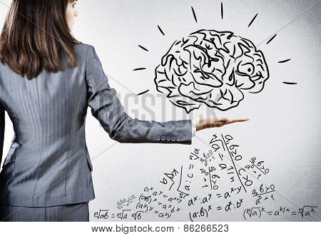 Rear view of businesswoman holding brain on palm