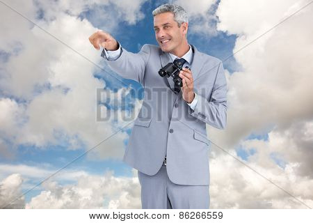 Businessman holding binoculars and pointing out something against blue sky with white clouds