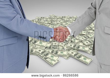 Side view of shaking hands against pile of dollars