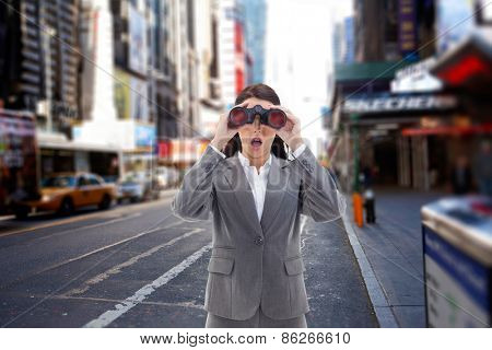 Surprised businesswoman looking through binoculars against blurry new york street