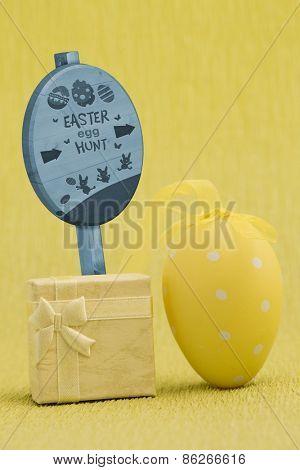 Easter egg hunt sign against a gift and an easter egg