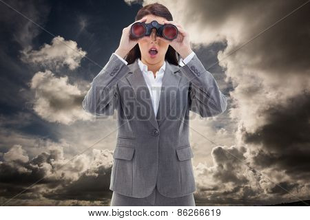 Surprised businesswoman looking through binoculars against dark sky with white clouds