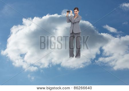Businesswoman posing with binoculars against cloudy sky