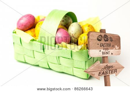 Easter egg hunt sign against speckled colourful easter eggs in a basket