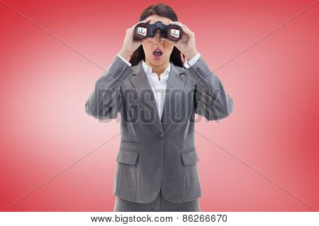 Surprised businesswoman looking through binoculars against red vignette