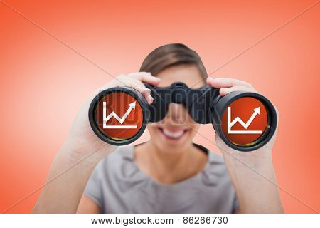 Woman looking through spyglasses against orange