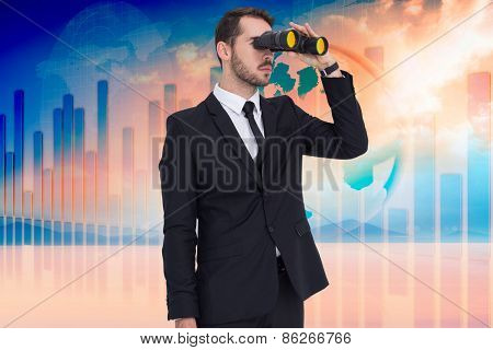 Businessman holding a briefcase while using binoculars against desert landscape