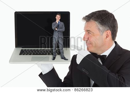 Thinking businessman against waiter pointing to laptop