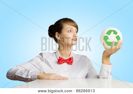 Young woman holding ball with recycle sign