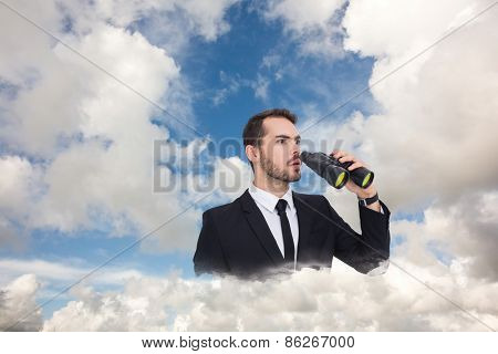 Surprised businessman standing and holding binoculars against blue sky with white clouds
