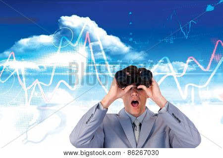 Suprised businessman looking through binoculars against bright blue sky with clouds