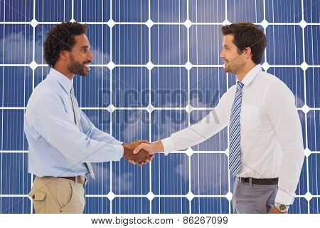 Smiling young businessmen shaking hands in office against solar panel